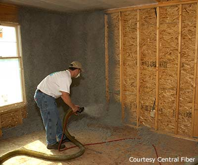 Insulation Contractor blowing in cellulose insulation into a wall