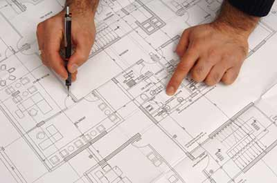 Architect reviewing house plans for specifying cellulose insulation